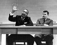 057 - Photo, Martin Luther King hand raised, sitting with John Maguire at desk in a classroom